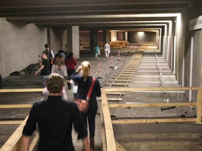"""Mehrere Menschen folgen einer Frau, die ganz in weiß gekleidet ist, auf die Bahnsteigebene der sogenannten """"Stillen Station"""" unter dem Raschplatz."""