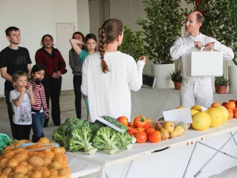 Eine Frau und ein Mann, beide ganz in weiß gekleidet, stehen an einer Tafel mit Obst und Gemüse. Im Hintergrund beobachten Erwachsene und Kinder den Dialog.