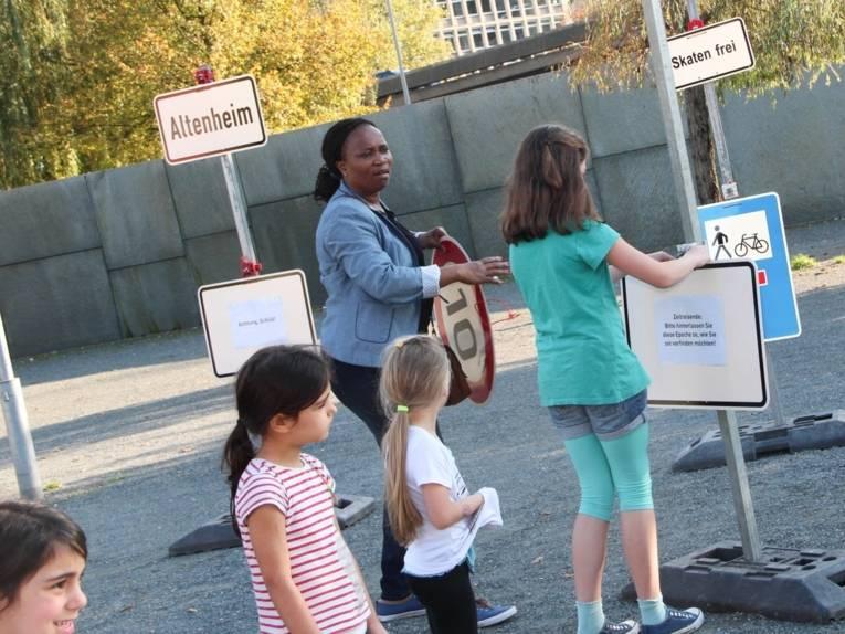 Eine Frau und ein Mädchen hängen Verkehrsschilder ab, die an provisorischen Schilderträgern befestigt sind. Im Vordergrund sieht man drei weitere Mädchen.