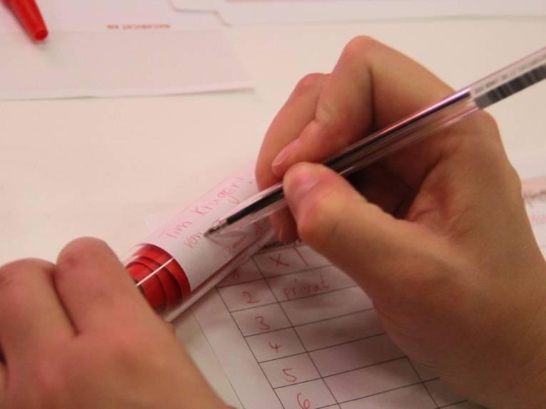 Ein durchsichtiges Röhrchen mit rotem Papier darin und zwei Hände, von denen die rechte mit rotem Stift das Röhrchen von außen beschriftet.