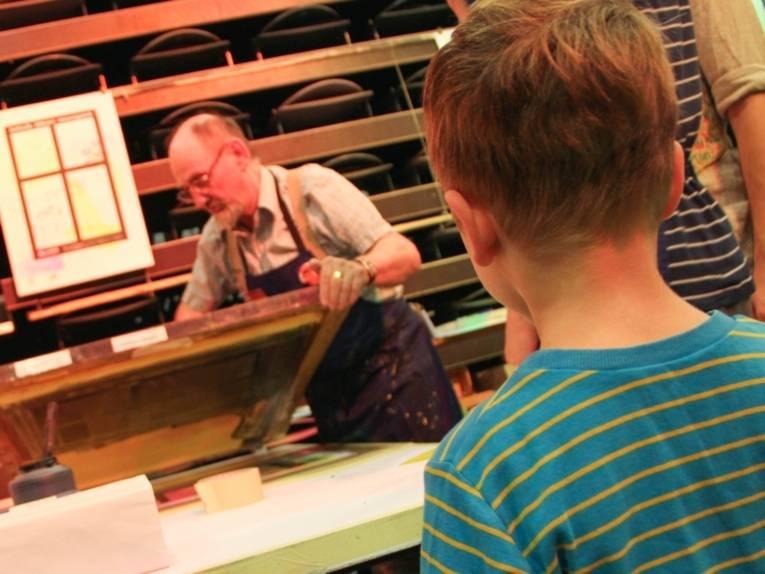 Ein älterer Herr mit Schürze bedruckt einen großen Papierbogen. Im Vordergrund steht ein Vorschulkind und beobachtet, was der ältere Herr tut.