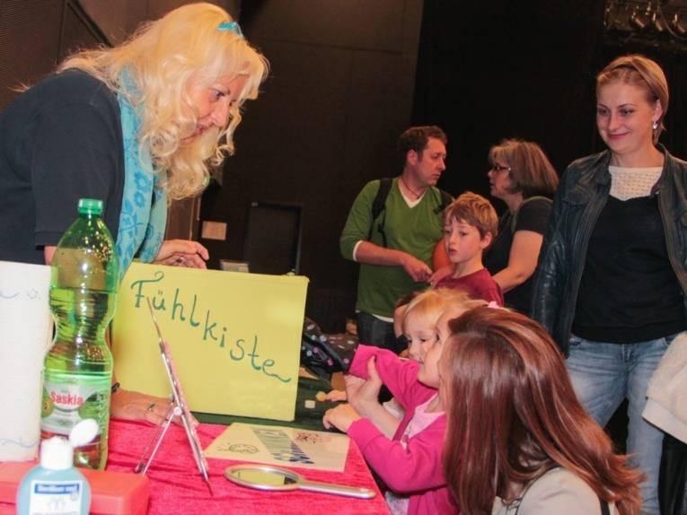 """Ein Mädchen steckt seine Hand in einen bunt gestalteten Karton, der mit der Aufschrift """"Fühlkiste"""" versehen ist."""
