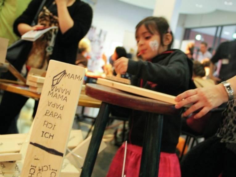 """Ein Mädchen bestempelt auf einem Barhocker eine Holzlatte. Im Vordergrund ist eine Holzlatte zu sehen, die bereits bestempelt wurde mit den Begriffen """"ich"""", """"Papa"""", """"Mama""""."""