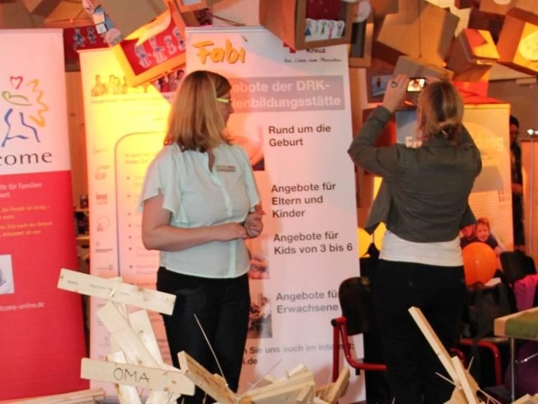 Zwei Frauen am Stand der Familienbildungsstätten. Im Hintergrund sieht man Roll-Ups mit Informationen zum Angebotsspektrum der Familienbildungsstätten.