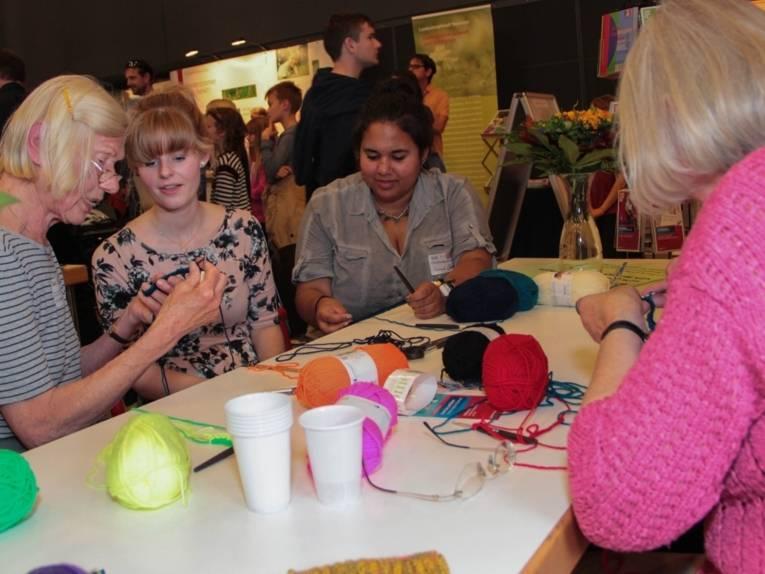 Zwei ältere Frauen sitzen mit zwei jungen Frauen um einen Tisch herum und zeigen ihnen, wie man strickt.