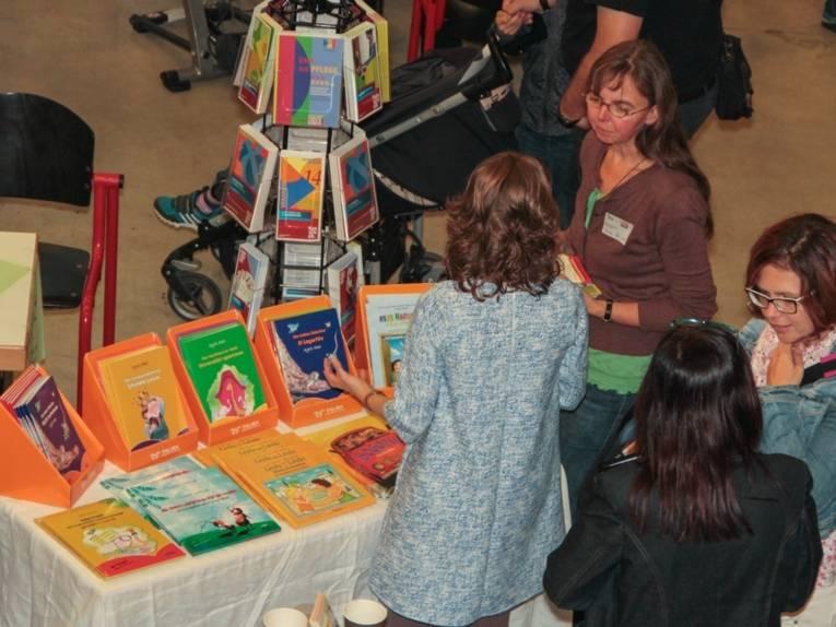 Vier Frauen im Gespräch vor einem Tisch, auf dem Kinderbücher ausgestellt sind.
