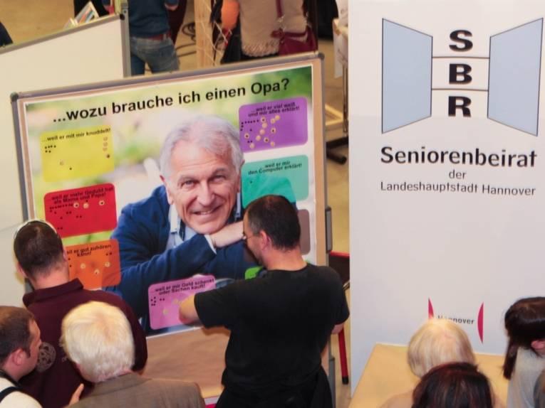 """Mehrere BesucherInnen stehen vor einem Plakat mit der Überschrift """"... wozu brauche ich einen Opa?"""". Auf verschiedenfarbigen Feldern kann mit Klebepunkten eine Markierung gesetzt werden, zum Beispiel """"... weil er viel weiß und mir alles erklärt."""""""