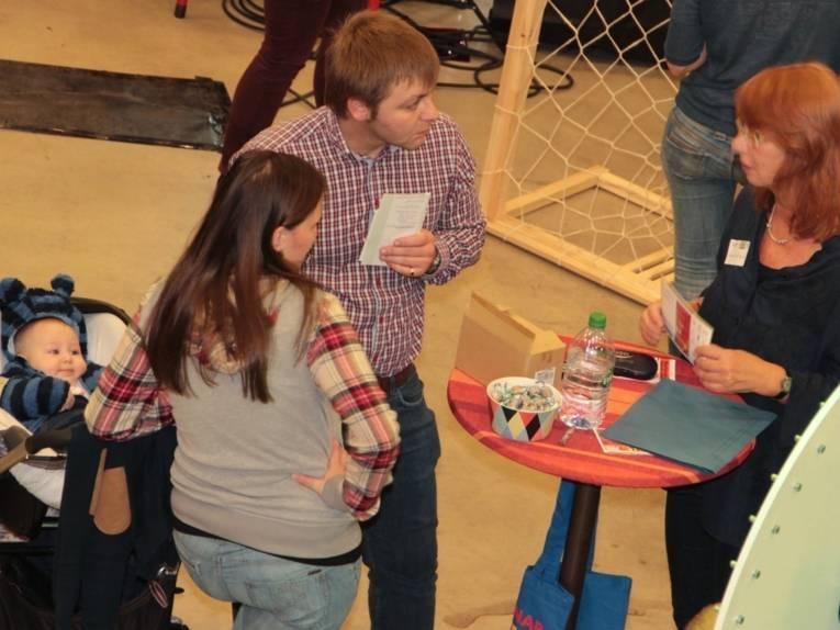 Eine Frau berät eine Frau und einen Mann mit Kleinkind im Kinderwagen an einem Stehttisch. Am rechten Bildrand ist ein Glücksrad zu sehen.