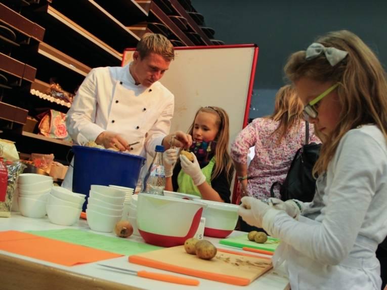 Ein Tisch mit zahlreichen großen und kleinen Schalen, Schneidebrettern und Messern. Ein Mann mit Koch-Arbeitskleidung zeigt einem Mädchen den Umgang mit einem Sparschäler am Beispiel einer Kartoffel. Im Vordergrund steht ein etwa sieben Jahre altes Mädchen und schält Kartoffeln.