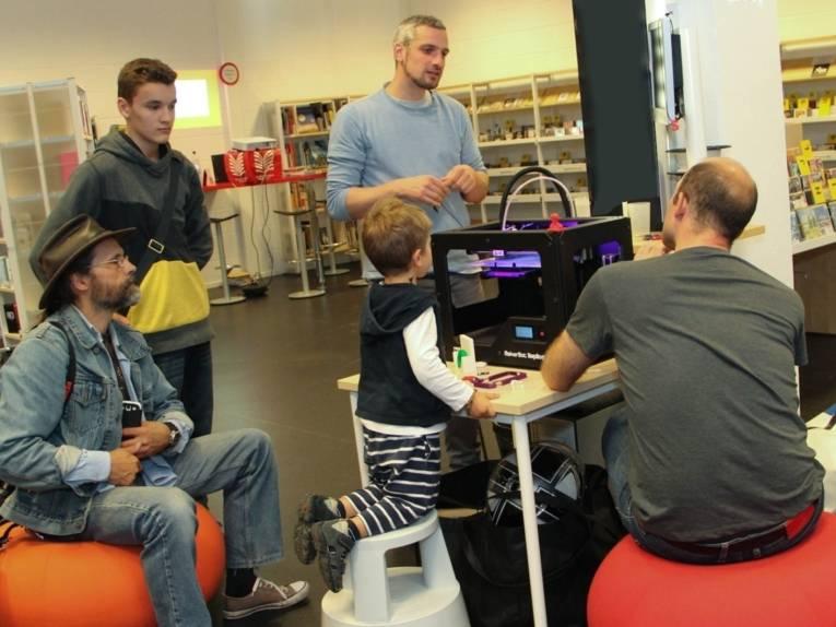 Ein 3D-Drucker in der Oststadtbibliothek, darum herum stehen, sitzen und knien fünf Jungen und Männer ganz unteschiedlichen Alters