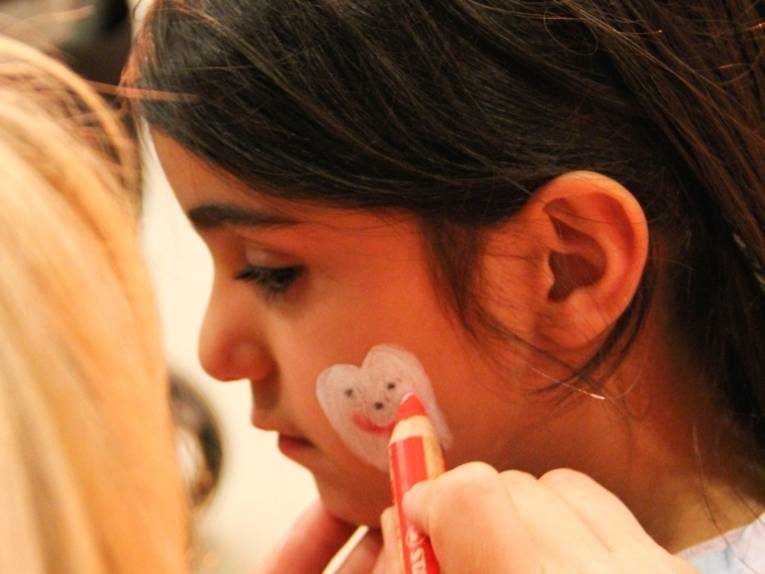 Eine Frau malt einem Mädchen mit Schminkstiften einen lachenden Zahn auf die linke Wange.
