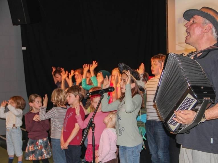 Der Kinderwaldchor mit etwa 15 Mädchen und Jungen steht vor der Bühne und singt. Manfred Kindel begleitet die Kinder mit dem Akkordeon.