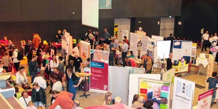 Stellwände von Ausstellern in einer großen Halle mit zahlreichen Besucherinnen und Besuchern