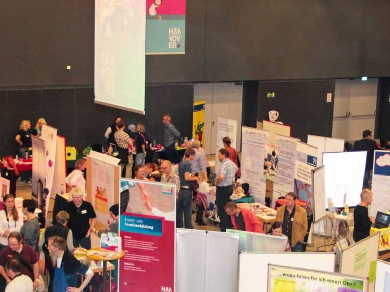 Informationsstände in einer großen Halle mit zahlreichen Besucherinnen und Besuchern