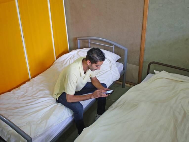 Ein Flüchtling liest Nachrichten auf seinem Handy