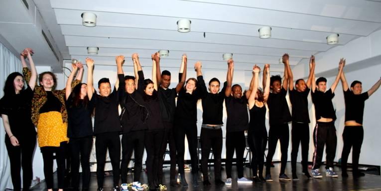 15 schwarz gekleidete Jegendliche stehen nebeneinander auf der Bühne im großen Saal der VHS, fassen sich an den Händen an und heben diese hoch.