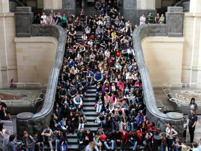 Etwa 200 Schüler/innen sitzen auf der Rathaustreppe und blicken Richtung Mitte der Kuppelhalle im Neuen Rathaus.