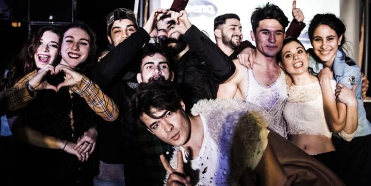 Zehn gut gelaunt aussehende Jugendliche stehen nebeneinander und posieren mit Gesten für die Kamera. Dabei formen sie Herzen mit den Händen, oder zeigen mit dem Daumen in die Luft. Einige davon umarmen sich.