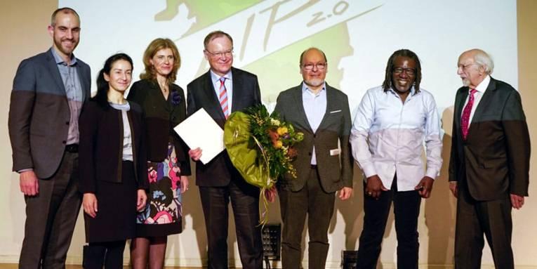 Sieben Personen - zwei Frauen und fünf Männer - stehen nebeneinander auf der Bühne im Europasaal des Hauses der Jugend. Ein Mann in der Mitte hält eine Urkunde in der Hand.