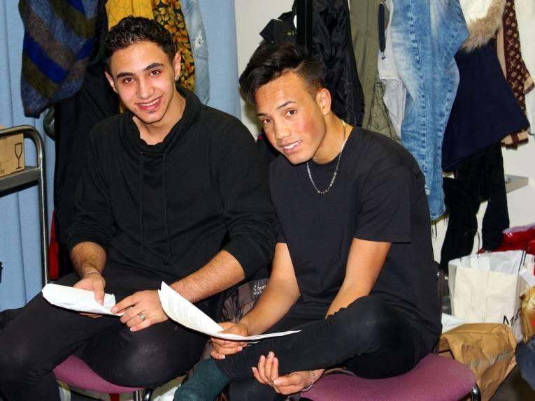 Zwei Jugendliche sitzen nebeneinander in einer Garderobe und halten Papiere in der Hand.