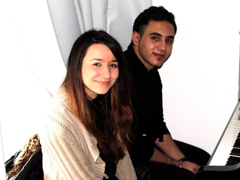 Zwei Jugendliche - ein Junge und ein Mädchen - sitzen vor einem Flügel und blicken in die Kamera.