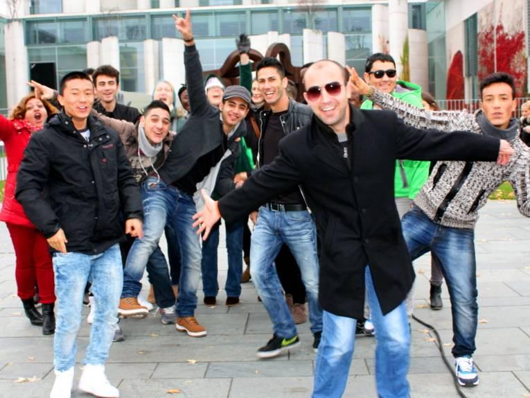 Etwa 20 Jugendliche und zwei Leiterinnen posieren vor der gläsernen Front des Kanzleramtes in Berlin.