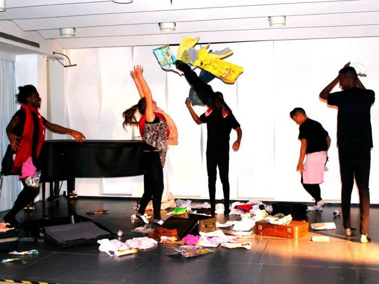Fünf Darsteller/innen tanzen über die Bühne und werfen dabei verschiedene Gegenstände wie Klamotten, Zeitungen und leere Dosen durch die Luft.