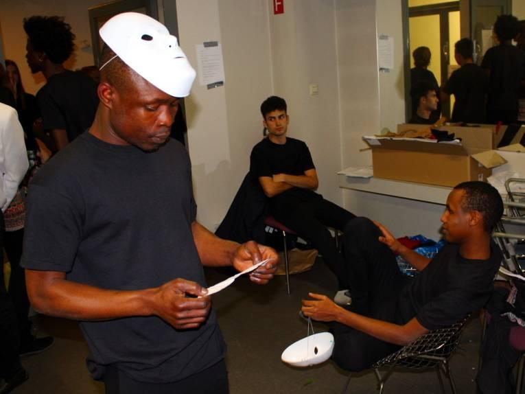 Zwei Jugendliche sitzen auf Stühlen und blicken entspannt durch den Raum. Ein Jugendlicher davor trägt eine über den Kopf geschnallte weiße Maske und schaut auf ein Papier in der Hand. Im Raum hängen Klamotten und Requisiten.