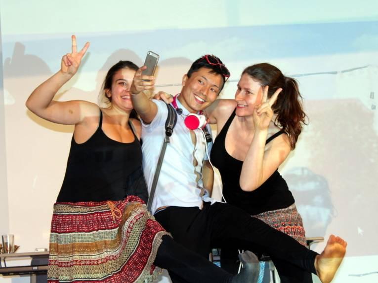 Drei Jugendliche - ein Junge in der Mitte und zwei Mädchen links und rechts - blicken lächelnd in ein Smartphone, dass der Junge zum Fotografieren hochhält.