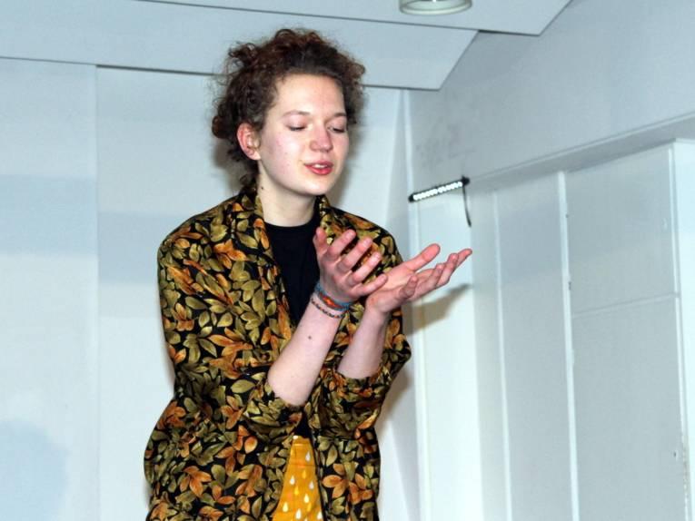 Eine Darstellerin hält beide Hände vor die Brust und schaut hinein, als hätte sie eine Kugel in der Hand.