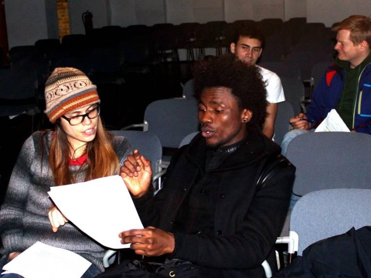 Zwei Personen sitzen nebeneinander in einer Stuhlreihe, schauen auf den gleichen Zettel und sprechen gleichzeitig.