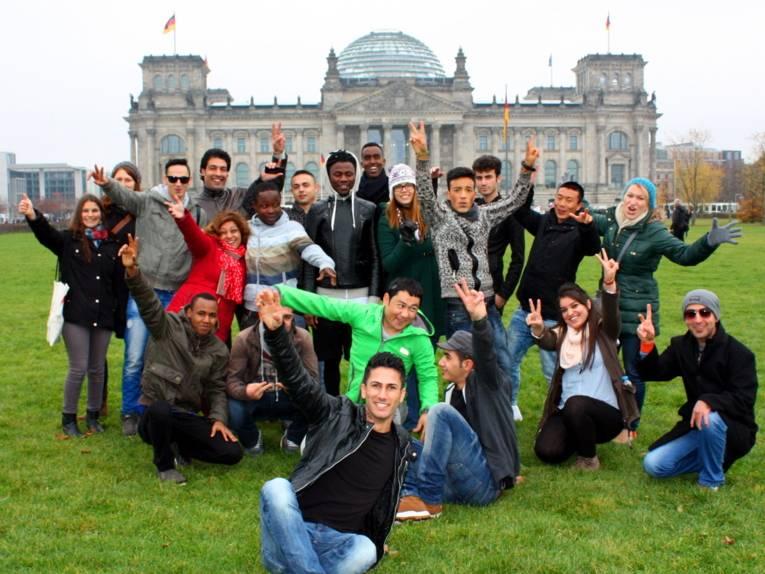 Eine 21-köpfige Gruppe posiert vor dem Bundestagsgebäude.
