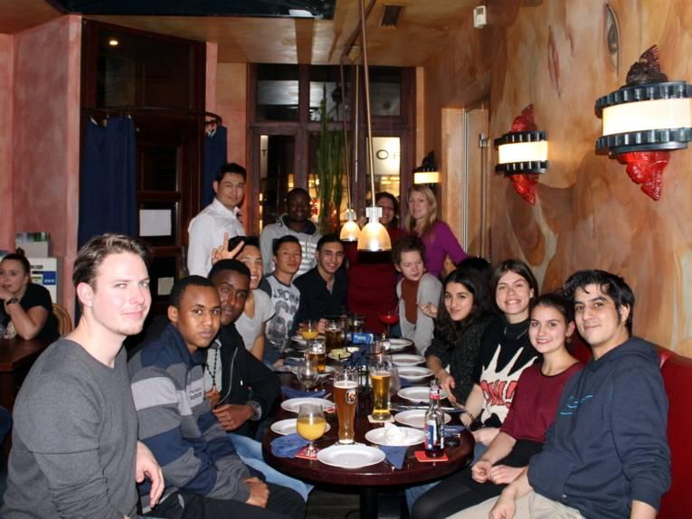 Etwa 20 Personen sitzen um einen langen Tisch, auf dem Getränkegläser und leere Teller stehen.