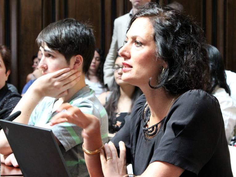 Eine Frau sitzt im Hodlersaal vor einem aufgeklappten Laptop und spricht. Dabei gestikuliert sie mit einer Hand.
