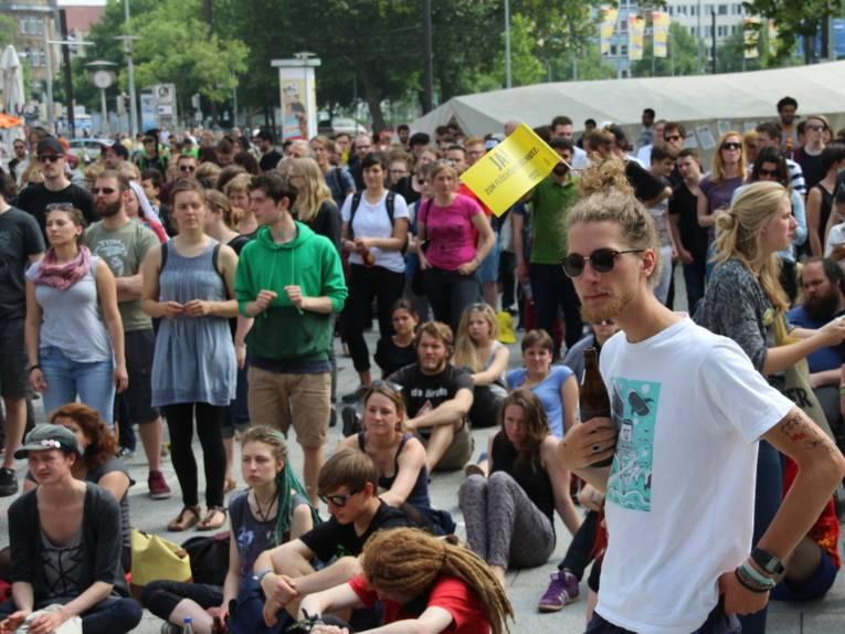 Ein Mann steht vor einer unüberschaubaren Menge von Menschen, die auf dem Goseriedeplatz unter freiem Himmel stehen und sitzen.
