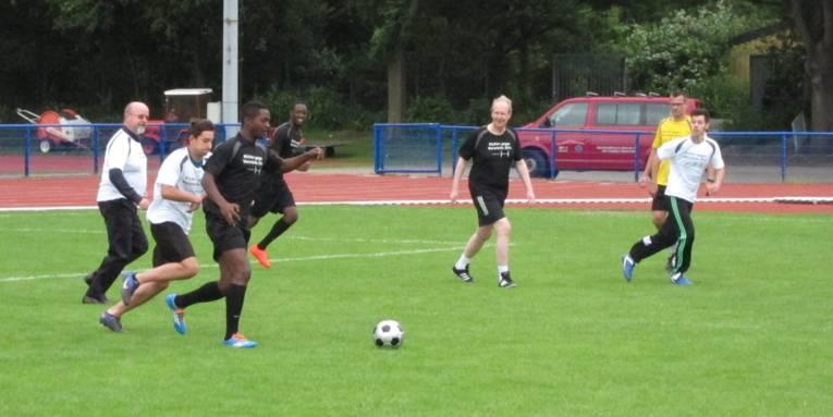Sieben Spieler/innen, darunter Oberbürgermeister Stefan Schostok und Polizeipräsident Volker Kluwe, jagen dem Ball nach.