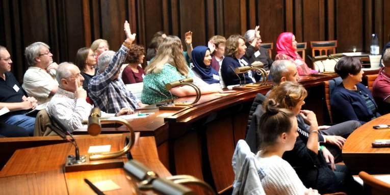 Etwa 30 Personen sitzen im Hodlersaal des Neuen Rathauses.