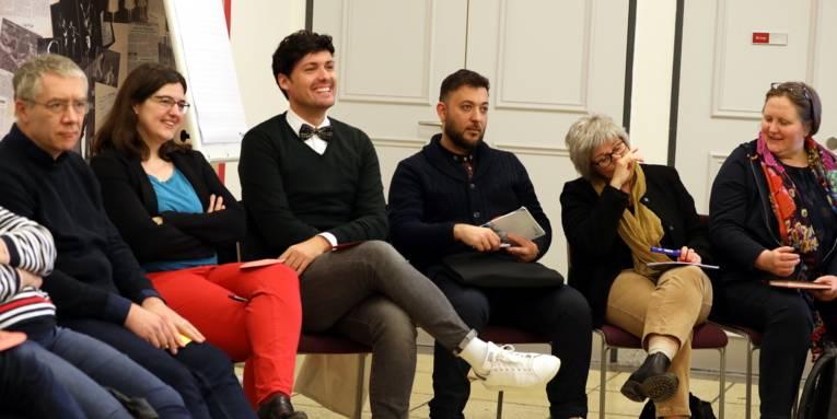 Sechs Personen - drei Männer und drei Frauen - sitzen im Foyer des Hauses der Jugend. Ein Mann in der Mitte lacht