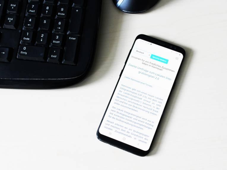 Symbolbild eines Smartphones, auf dessen Display die Startseite der Befragung angezeigt wird. Links danemen sieht man den Numblock einer Tastatur und darüber den Teil einer Mouse.