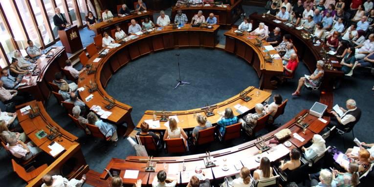 Von oben ist der Hdlersaal zu erkennen, in dem links im Bild der Oberbürgermeister vor einem Rednerpult steht. Die anderen Anwesenden sitzen kreisförmig in mehreren Reihen im Saal an Pulten oder in einfachen Tischreihen.