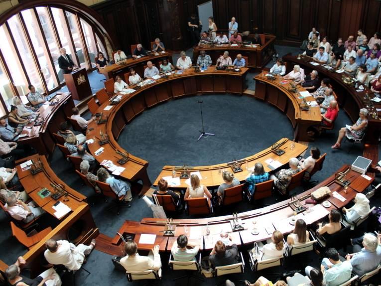 Im Hodlersaal sitzen neben kreisförmig aufgestellten Pulten Menschen. Links im Bild steht ein Mann an einem Stehpult und spricht.