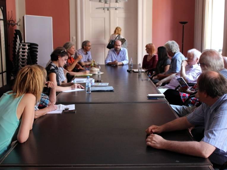 Etwa zehn Personen sitzen an einem langen Tisch im Raum Leipzig.