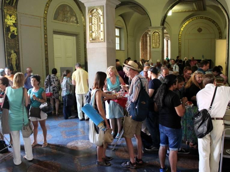 Etwa 70 Personen stehen im Flur des Neuen Rathauses an Stehtischen. Viele davon trinken und essen.
