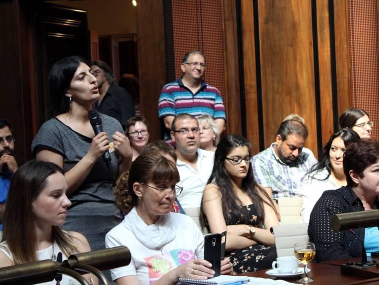 Eine Frau steht im Hodlersaal und spricht. Um sie herum sitzen weitere Teilnehmer/innen.
