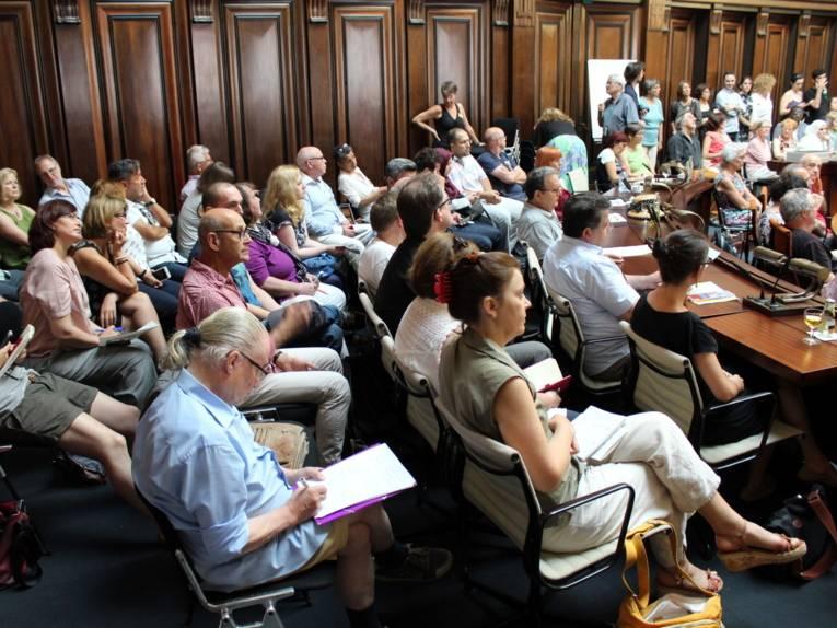 Etwa 40 Personen sitzen in mehreren Reihen im Hodlersaal.
