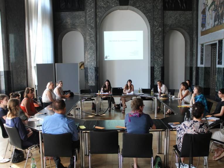 Etwa 20 Personen sitzen im Mosaiksaal um rechteckig aufgestellte Tische.