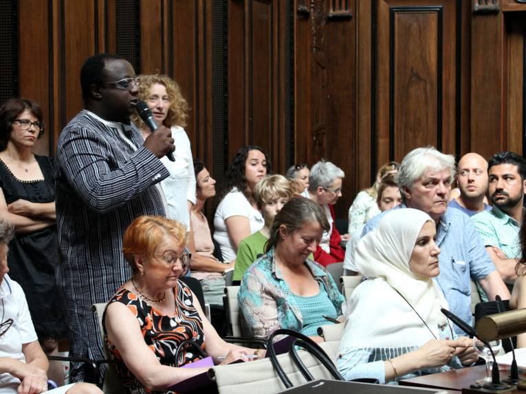 Ein Mann steht im Hodlersaal und spricht. Um ihn herum sitzen weitere Teilnehmer/innen.