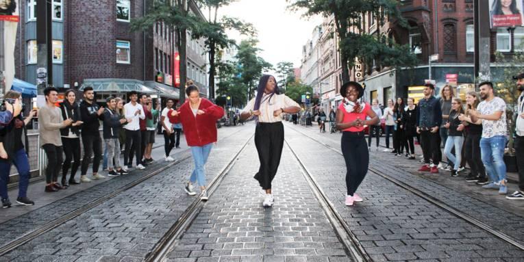 Etwa 20 Jugendliche stehen in zweit Linien am Rand einer Straße. In der Mitte stehen drei Mädchen nebeneinander und überkreuzen die Füße, um einen Seitwärtsschritt zu machen.