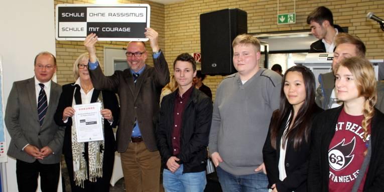 Acht Personen, vier Erwachsene und vier Jugendliche stehen nebeneinander in einer Reihe. Ein Mann hält ein Schild mit dem zweifarbigen Logo der Kampagne hoch.