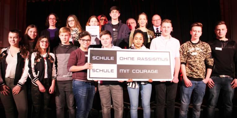 Etwa 20 Personen stehen in zwei Reihen nebeneinander. Die Jugendlichen in der vorderen Reihe halten das zweifarbige Banner der Kampagne vor sich.